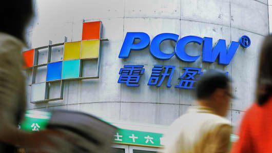 People walk past a PCCW sign in Hong Kong.