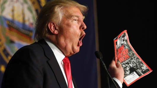 Republican Presidential candidate Donald Trump shows off a Time magazine with a cover story titled, 'How Trump Won'
