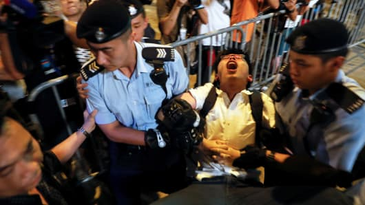 Student protest leader Joshua Wong shouts as he is carried by policemen as protesters are arrested at a monument symbolizing the city's handover from British to Chinese rule, a day before Chinese President Xi Jinping is due to arrive for the celebrations, in Hong Kong, China June 28, 2017.