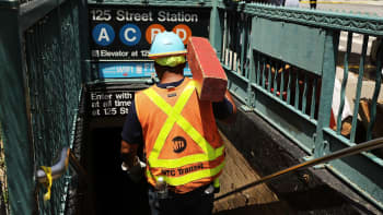 A Metropolitan Transportation Authority worker enters a Harlem subway station where a morning train derailment occurred on June 27, 2017, in New York City.