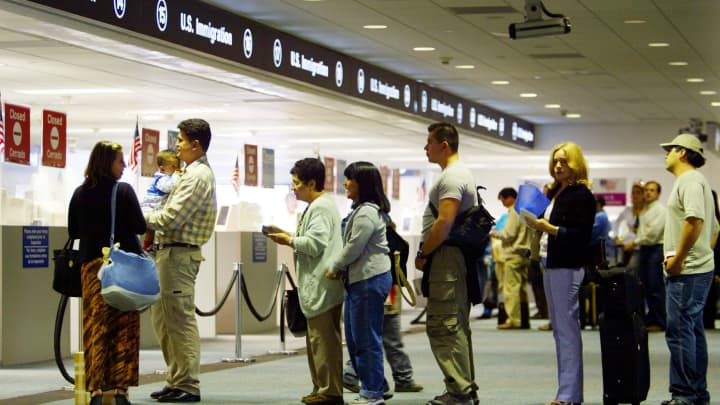 People wait in line to have their passports checked by Immigration inspectors July 2, 2002 at Miami International Airport in Miami, Florida