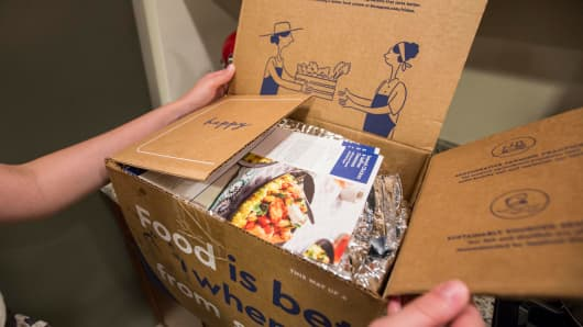 A Blue Apron customer unpacks a Blue Apron box.