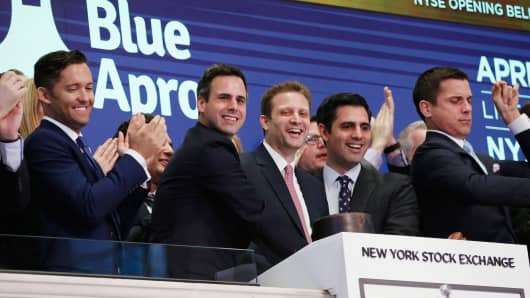 Blue Apron CEO Matthew B. Salzberg, center, celebrates with co-founders Ilia Papas, second from right, and Matt Wadiak during the company's IPO on the New York Stock Exchange in New York, June 29, 2017.