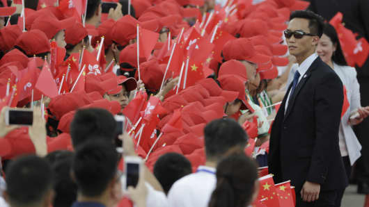 A security official stands in front of attendees waving the flags of China and Hong Kong ahead of Chinese President Xi Jinping's arrival at Hong Kong International Airport on June 29, 2017.