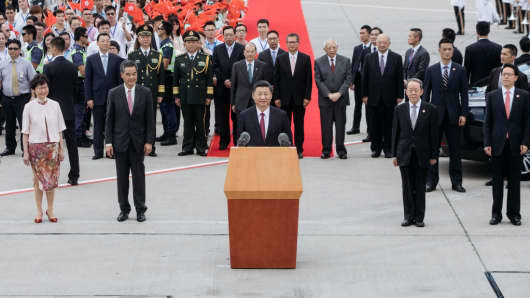 Chinese President Xi Jinping speaks as Carrie Lam, Hong Kong's chief executive-elect (left) and Leung Chun-ying, Hong Kong's outgoing chief executive (second left) look on following Xi's arrival at Hong Kong International Airport on June 29, 2017.