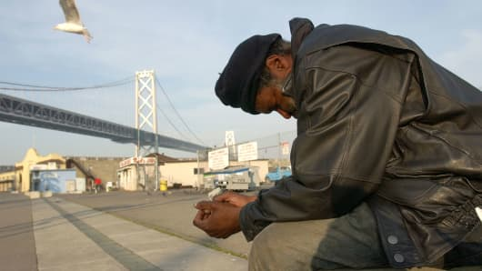 A homeless man sits by the waterfront with the San Francisco Bay Bridge in the background in San Francisco, California.