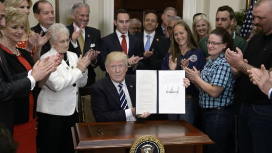 President Donald Trump shows off his executive order that aims to expand apprenticeships to train people for millions of unfilled skilled jobs. The order doubles the funding for apprenticeship grants, to $200 million, by reallocating money from existing job-training programs.