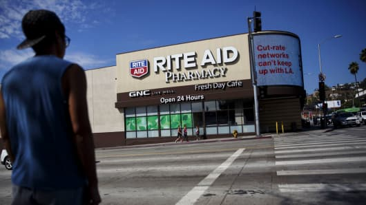 A pedestrian crosses the street in front of a Rite Aid store in Los Angeles.