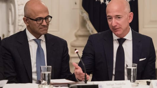 Microsoft CEO Satya Nadella (C) listens to Amazon CEO Jeff Bezos during an American Technology Council roundtable at the White House in Washington, DC.