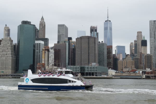 A ferry passes by the skyline of lower Manhattan.