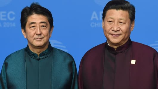 Japan's Prime Minister Shinzo Abe (L) poses with Chinese President Xi Jinping.