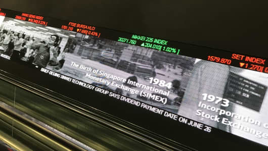 An escalator past an electronic screen and ticker board at the Singapore Exchange.