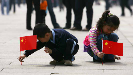 Children holding Chinese national flag play in Tiananmen Square in Beijing, China.