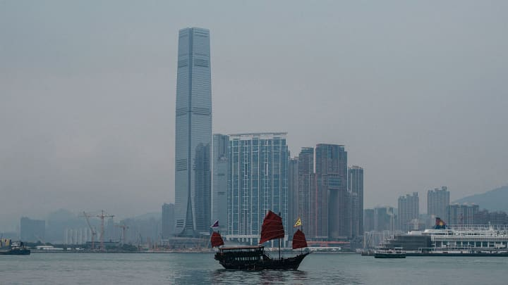 A junk boat sails past the International Commerce Centre left and other buildings in Hong Kong China