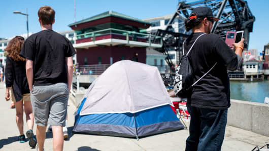 People walk casually past a tent which is part of a homeless encampment in San Francisco.