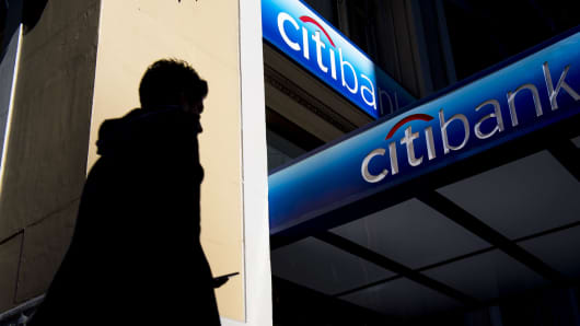 The silhouette of a pedestrian holding a mobile device is seen walking past a Citigroup bank branch in San Francisco.