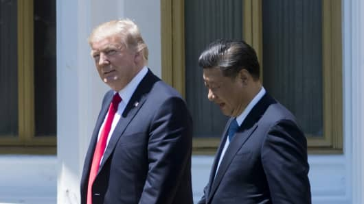 President Donald Trump (L) and Chinese President Xi Jinping walk together at the Mar-a-Lago estate in West Palm Beach, Florida, April 7, 2017.