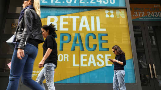 People walk by empty retail space in lower Manhattan in New York City.
