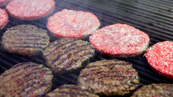 Hamburgers cook on a grill in the kitchen of an h3 Hamburger Co. restaurant in Lisbon, Portugal, on Saturday, March 3, 2012.