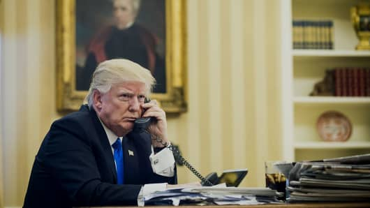 U.S. President Trump speaks on the phone in the Oval Office.