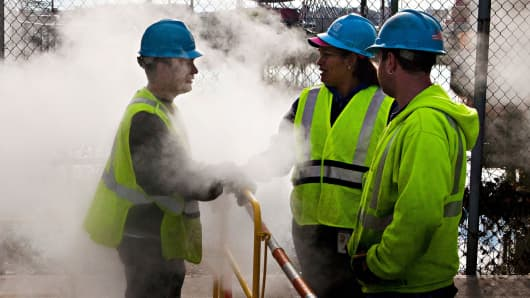 Con Edison employees confer while working on a steam pipe on First Avenue in New York City.