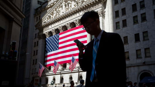 A pedestrian views a mobile device while walking past an American flag displayed outside of the New York Stock Exchange in New York.