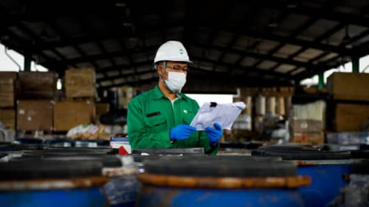 A technician inspecting chemical waste at a plant in Malaysia.