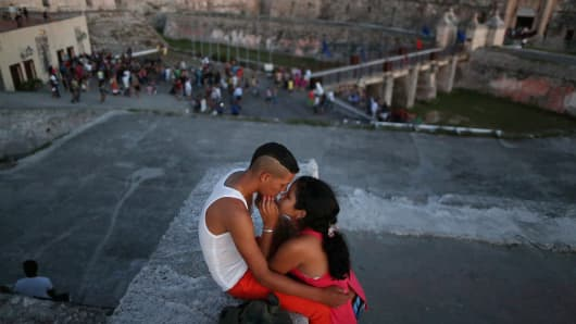 A young couple kiss on top of the fortifications of El Castillo del Morro, an old Spanish fort that stands at the mouth of the Port of Havana