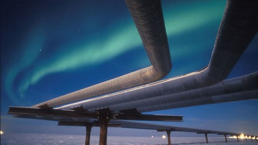 A full moon helps illuminate an Alaskan pipeline under the faint glow of the Aurora Borealis on November 19, 2002 near Milne Point, Alaska.