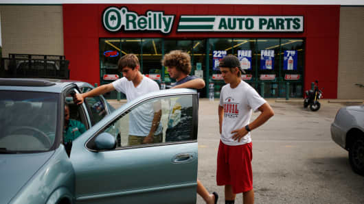 Customers watch as an employee investigates their vehicle outside an O'Reilly Automotive auto parts store in Louisville, Kentucky.
