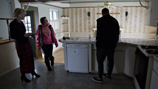 A real estate agent, left, shows first time home buyers the kitchen area inside a home for sale in Warren, Michigan.