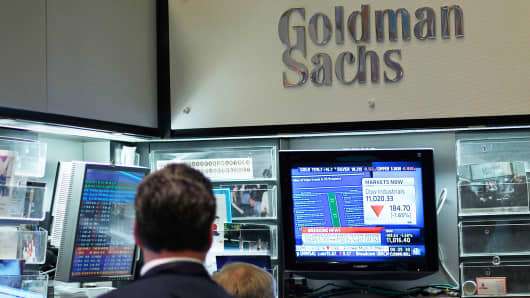 Financial professionals sit in the Goldman Sachs booth on the floor of the New York Stock Exchange.