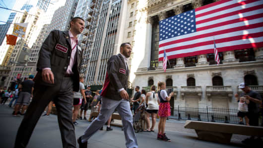 Traders pass in front of an American flag displayed outside of the New York Stock Exchange in New York.