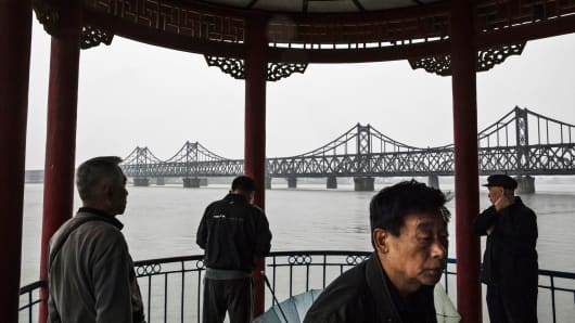 The 'Friendship Bridge' is seen in the background as Chinese men take part in morning exercises on the Yalu river in the border city of Dandong, Liaoning province, northern China across from the city of Sinuiju, North Korea on May 23, 2017 in Dandong, China.