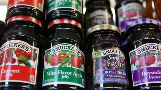 Smuckers fruit products are displayed on a shelf at a grocery store.
