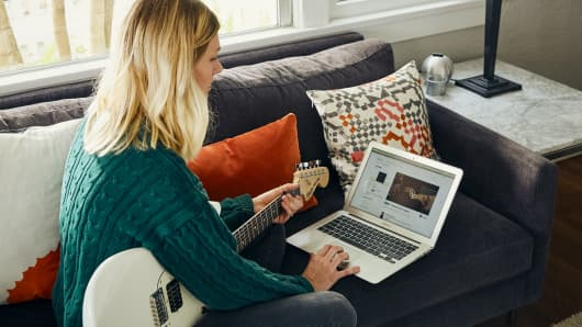 A woman uses the Fender Play program to learn how to play guitar.