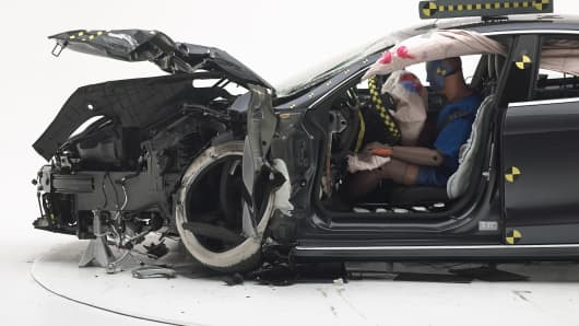 The dummy's position in relation to the door frame, steering wheel, and instrument panel after the second crash test indicates that the driver's survival space was maintained reasonably well overall.