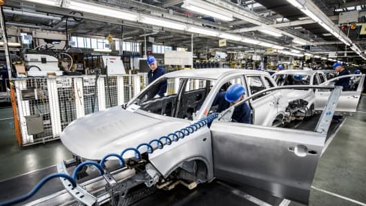 Employees work on the body shell of an automobile on the production line inside the Suzuki Motor Corp. plant in Esztergom, Hungary