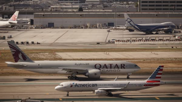 A Qatar Cargo Boeing 777F plane and an American Airlines Airbus 321 prepare for take off at Los Angeles International Airport in Los Angeles, California.