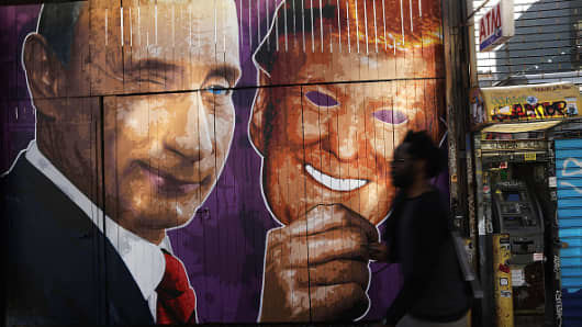A mural depicting a winking Vladimir Putin taking off his Donald Trump mask is painted on a storefront outside of the Levee bar in Brooklyn on February 25, 2017 in New York City.
