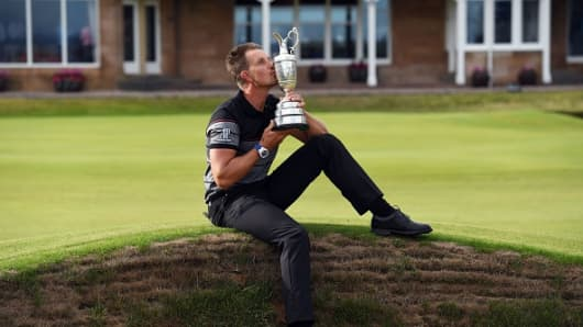 Sweden's Henrik Stenson poses for pictures in front of the clubhouse as he kisses the Claret Jug, the trophy for the Champion golfer of the year after winning the 2016 British Open Golf Championship at Royal Troon in Scotland on July 17, 2016.