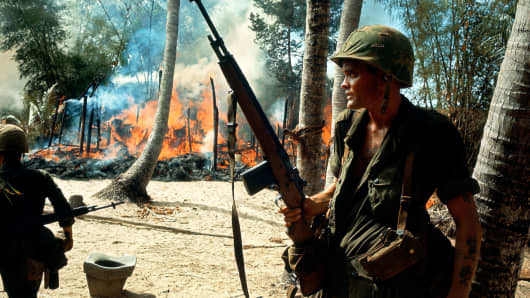 American soldiers in a burning village, Vietnam, circa 1965.