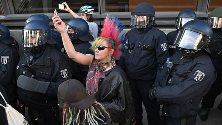 A female punk holds up her phone surrounded by riot police during the 'Welcome to Hell' protest march on July 6, 2017 in Hamburg, Germany.