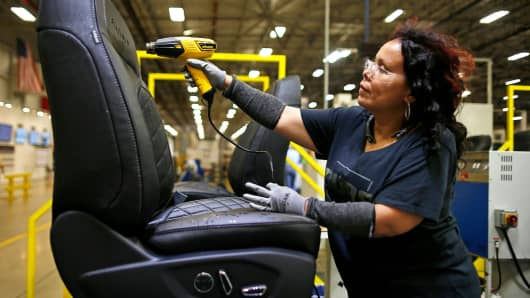 A worker uses a heat gun to smooth out the wrinkles on a car seat during production at the Lear Corp. manufacturing facility in Hammond, Indiana.