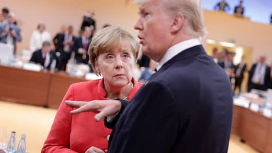 U.S. President Donald Trump talks to German Chancellor Angela Merkel before the first working session of the G20 meeting in Hamburg, Germany, July 7, 2017.