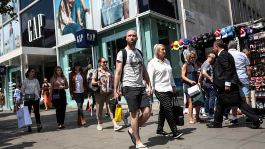 Shoppers walk past a Gap Inc. clothing store in London, U.K., on Thursday, May 25, 2017.