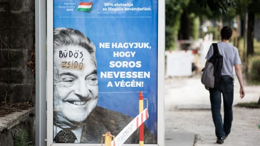"Billboard campaign by the Hungarian government shows George Soros smiling next to the words ""Let's not let Soros have the last laugh."" The graffiti translates to ""dirty Jew."""