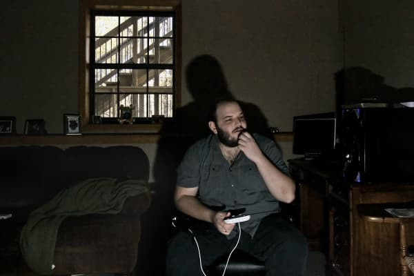 Zachary Brame, plays a video game in the basement at his parents' home in Kansas City, Kansas.