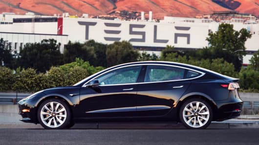 Elon Musk hands over first 30 Tesla Model 3s