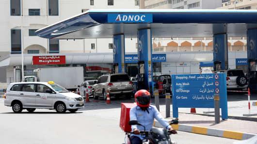 A man rides a motorcycle near an ADNOC petrol station in Abu Dhabi, United Arab Emirates July 10, 2017.
